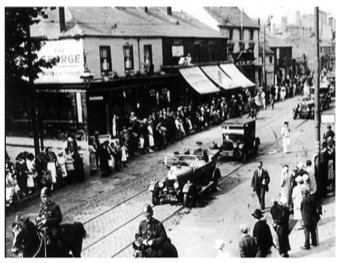 B+W photo of George Inn Public House and High Street 1900s showing a procession of cars led by two horse mounted police officers people line the route