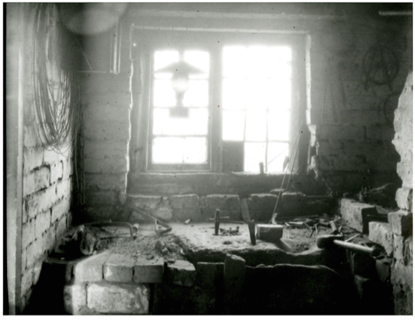 B+W image of the interioe of anAwl Blade maker's workshop Sandbank Bloxwich 1915. Tools, lamp stone block