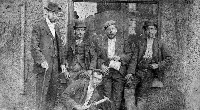 Bloxwich miners drinking at the Spring Cottage c1890s 4 men stand on crouches with pick axe.